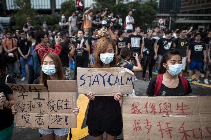 Demonstrators display placards as they gather near a ceremony marking China's 65th National Day in Hong Kong on October 1, 2014. (AFP Photo)
