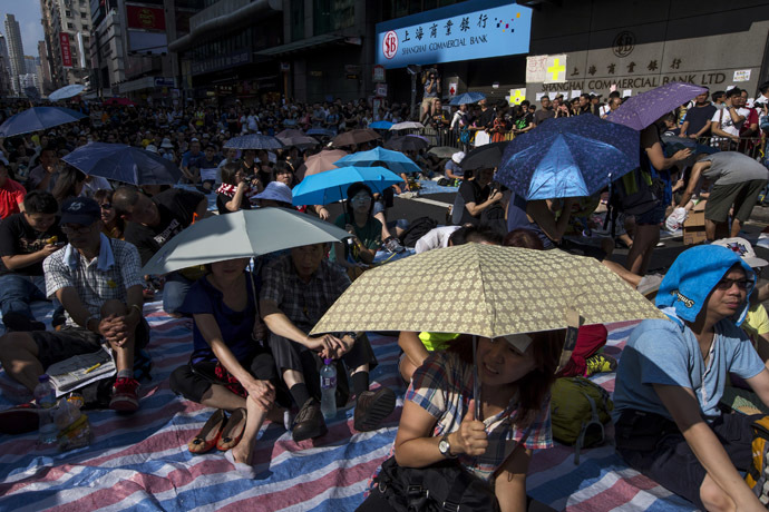 Protesters sit under umbrellas at a main street at Mongkok shopping district after thousand of protesters blocked the road in Hong Kong October 1, 2014. (Reuters/Tyrone Siu)