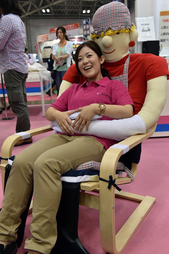 "An employee of Japan's nursing care goods maker Unicare demonstrates an easy chair for congnitively empaired persons ""Yasuragi chair"" at the annual International Home care and Rehabilitation exhibition in Tokyo on October 1, 2014. (AFP Photo)"