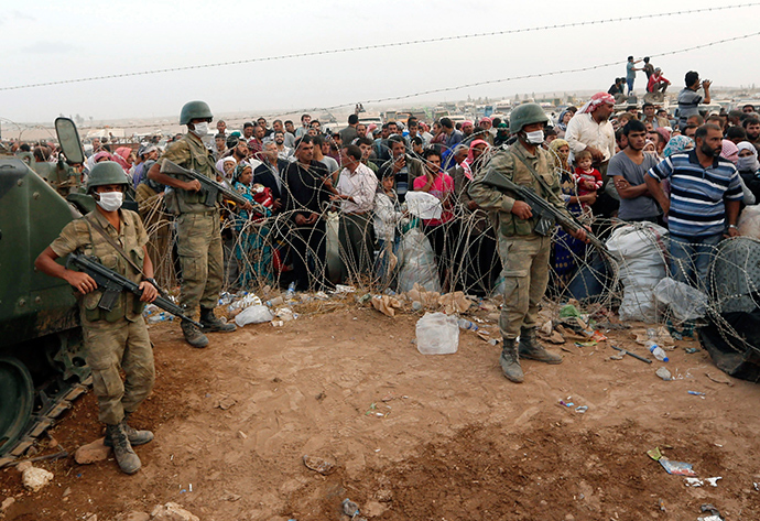 Turkish soldiers stand guard as Syrian Kurdish refugees wait behind the border fences to cross into Turkey near the southeastern town of Suruc in Sanliurfa province September 27, 2014 (Reuters / Murad Sezer)