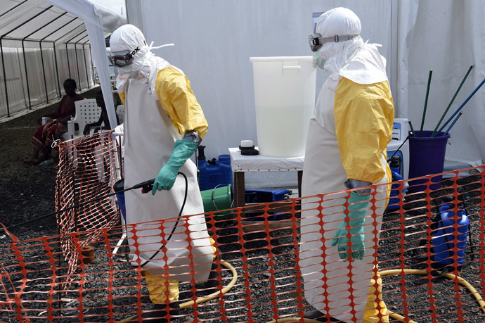 A health worker in protective suit carries equipment on October 1, 2014 at MSF's (Doctors Without Borders) Ebola treatment center in Monrovia. (AFP Photo)