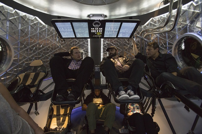 SpaceX CEO Elon Musk (L) sits with guests inside the Dragon V2 spacecraft (Reuters/Mario Anzuoni)