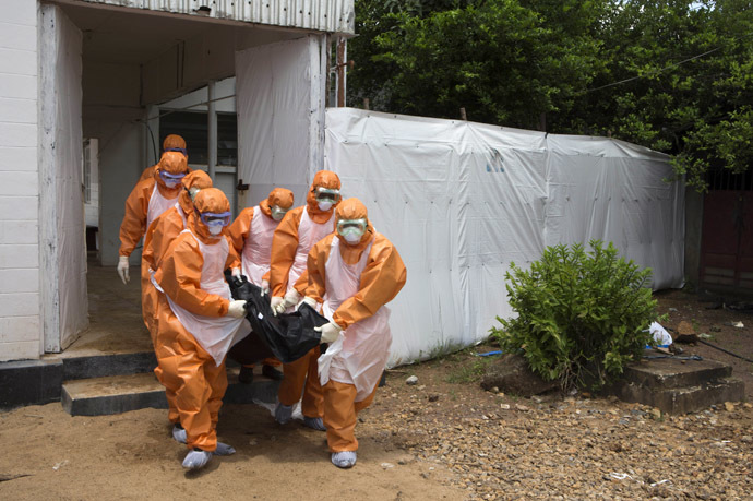 A burial team wearing protective clothes, remove a body from an isolation holding centre, for people waiting for laboratory results, at the Port Loko District Hospital September 27, 2014. (Reuters/Christopher Black/WHO)