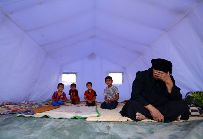A family, who fled from the violence in Mosul, sits inside a tent at a camp on the outskirts of Arbil in Iraq's Kurdistan region, June 12, 2014. (Reuters / Stringer)