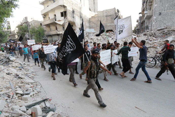 """Supporters of Al-Qaeda's Syria affiliate Al-Nusra Front hold placards calling Syrian President Bashar al-Assad a """"terrorist"""" and denouncing Arab states that have joined anti-Islamic State group campaign, as they demonstrate in the northern city of Alepppo on September 24, 2014. (AFP Photo / Zein Al Rifai)"""