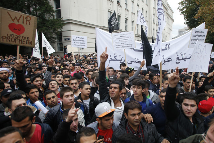 Austrian Muslims carry banners and shout slogans during a protest against a film made in the U.S. and cartoons published by a French magazine that denigrate Islam's Prophet Mohammad, in Vienna September 22, 2012. (Reuters/Leonhard Foeger)