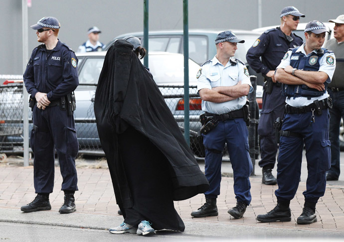Police officers stand on guard next to a woman wearing a burqa near the venue where controversial Dutch member of parliament Geert Wilders will speak in the Sydney suburb of Liverpool February 22, 2013. (Reuters/Daniel Munoz)