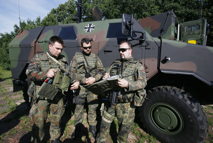 Three Bundeswehr army soldiers stand in front of a 'Dingo`, a German armored vehicle made by Krauss-Maffei Wegmann (KMW), at the Joint Support Service base in Grafschaft near the western German city of Bonn July 12, 2011. (Reuters/Wolfgang Rattay)