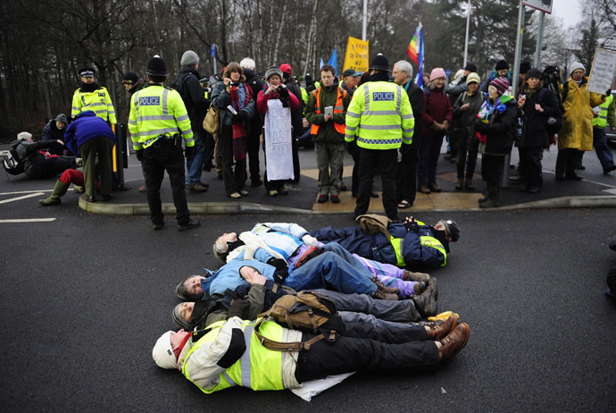 Anti-nuclear demonstrators lie in the road outside a gate of the Atomic Weapons establishment (AWE) at Aldermaston in southern England February 15, 2010. (Reuters/Kieran Doherty)