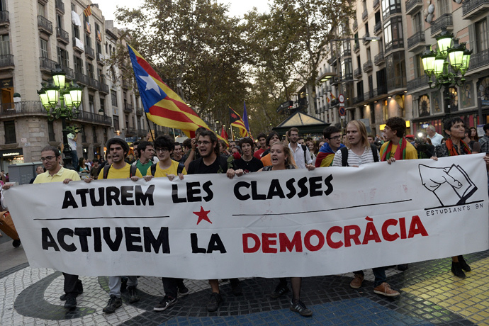 "Students hold a banner reading ""stop the class, start the democracy"" as they protest Spain's constitutional court ruling stopping Catalonia from holding an independence referendum, in Barcelona on October 2, 2014. (AFP Photo / Josep Lago)"