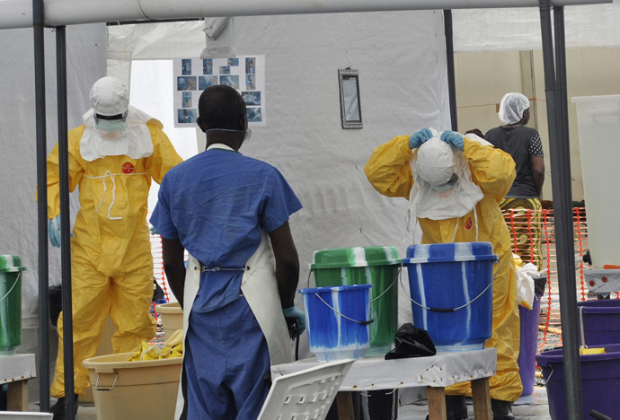 A Doctors Without Borders health worker takes off his protective gear under the surveillance of a colleague at a treatment facility for Ebola victims in Monrovia September 29, 2014. (Reuters/James Giahyue)