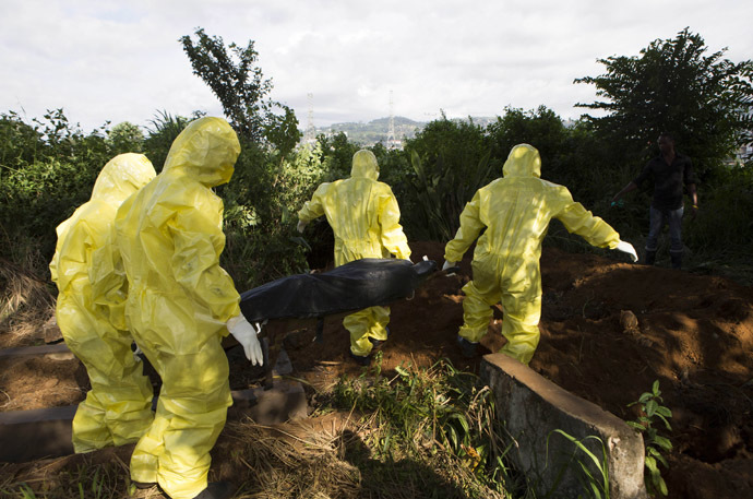 A burial team wearing protective clothing prepare the body of a person suspected to have died of the Ebola virus for interment, in Freetown September 28, 2014. (Reuters/Christopher Black)