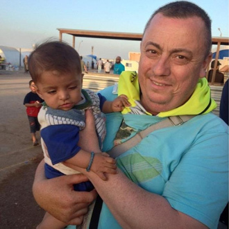 Handout image received from Britain's Foreign and Commonwealth Office on September 15, 2014 shows British aid worker, Alan Henning holding a child in a refugee camp on the Turkish-Syrian border. (AFP Photo / Foreign and Commonwealth Office)
