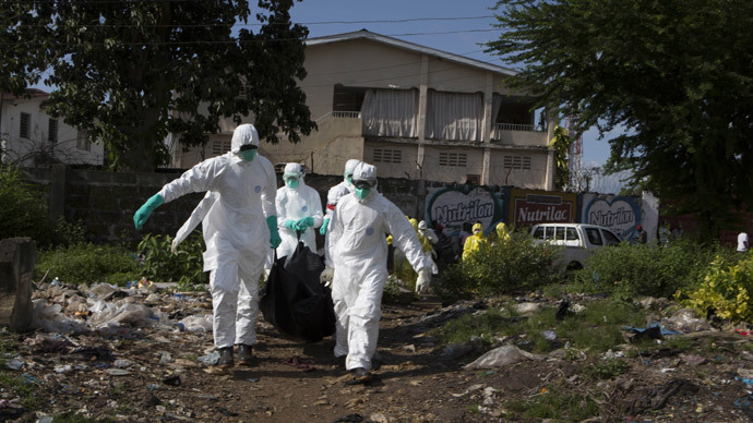 A burial team wearing protective clothing, remove a body of a person suspected of having died of the Ebola virus, in Freetown September 28, 2014.(Reuters / Christopher Black)