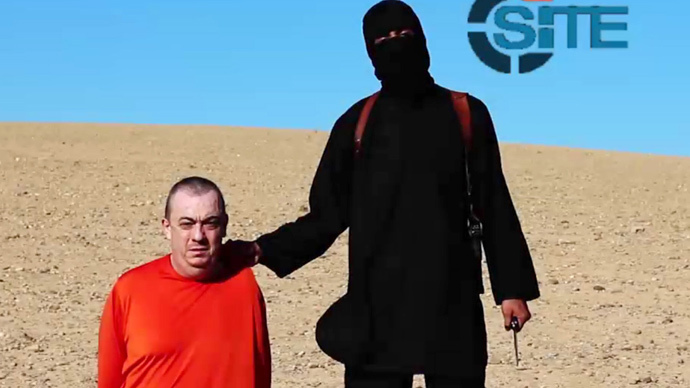 Masked militant (R) threatening to execute British hostage Alan Henning dressed in orange and on his knees in a desert landscape (AFP Photo / Site Intelligence Group / HO)