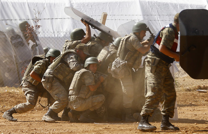 Turkish soldiers take cover from stone throwing Turkish Kurdish protesters near the Mursitpinar border crossing on the Turkish-Syrian border in the Turkish town of Suruc in southeastern Sanliurfa province October 4, 2014. (Reuters/Murad Sezer)