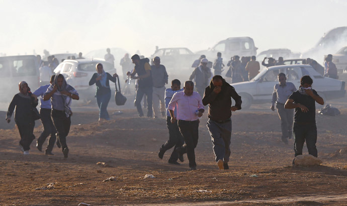 Turkish Kurdish protesters run from tear gas fired by Turkish soldiers near the Mursitpinar border crossing on the Turkish-Syrian border, in the Turkish town of Suruc in southeastern Sanliurfa province October 4, 2014. (Reuters/Murad Sezer)