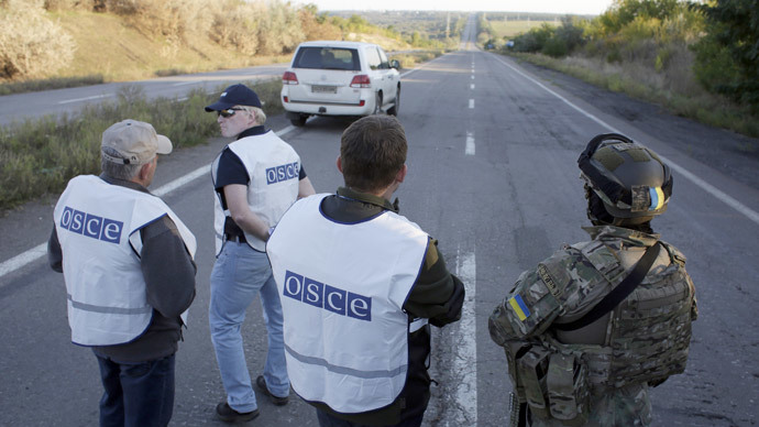 A Ukrainian serviceman (R) and OSCE observers wait on a road near Donetsk.(AFP Photo / Anatolii Stepanov)