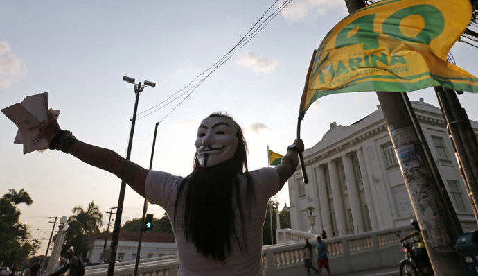 A supporter of Brazilian Socialist Party (PSB) presidential candidate Marina Silva, with a Guy Fawkes mask strapped to the back of her head, waves a campaign flag in front of the Rio Branco Palace in Rio Branco, Acre state October 3, 2014. (Reuters/Sergio Moraes)