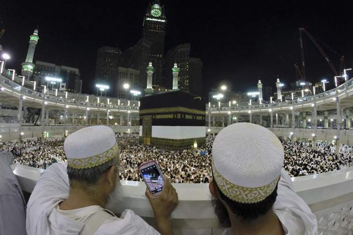 Muslim pilgrims take pictures for the pilgrims as they pray around the holy Kaaba at the Grand Mosque, during the annual haj pilgrimage in Mecca October 1, 2014. (Reuters/Muhammad Hamed)