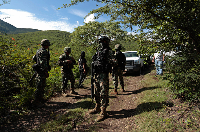 Soldiers guard an area where a mass grave was found, in Colonia las Parotas on the outskirts of Iguala, in Guerrero October 4, 2014 (Reuters / Jorge Dan Lopez)