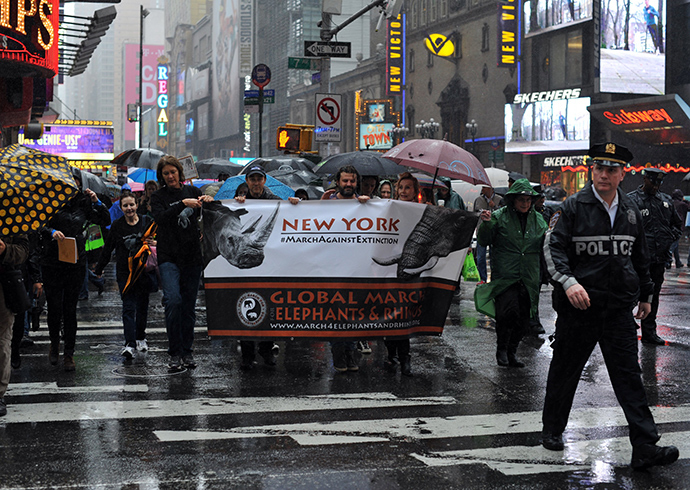 Protesters march across 42nd Street during the official Global March for Elephants and Rhinos rally in New York on October 4, 2014 (Reuters / Timothy A. Clary)