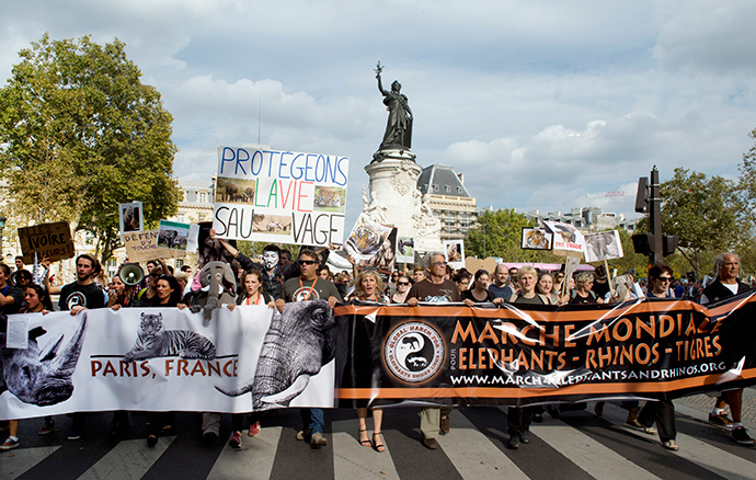"Protesters hold a sign reading ""Let's protect wildlife"" as they take part in a demonstration in Paris as part of the Global March for Elephants, Rhinos and Lions on October 4, 2014 (AFP Photo / Alain Jocard)"