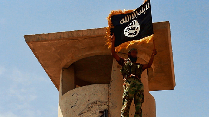 A militant of the Islamic State of Iraq and the Levant (ISIL) posing with the trademark Islamists flag after they allegedly seized an Iraqi army checkpoint in the northern Iraqi province of Salahuddin (AFP Photo / HO)