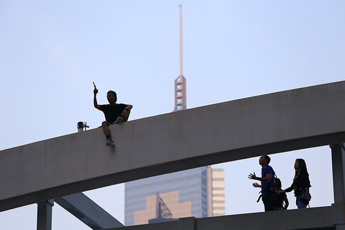 A man who said his three children couldn't go to school because of road blockages brought on by the occupy movement sits in protest on top of a pedestrian bridge in Hong Kong on October 5, 2014 (AFP Photo / Aaron Tam)