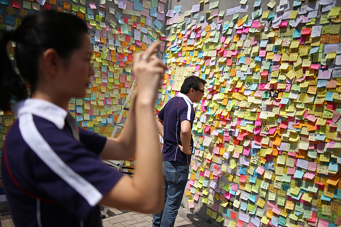 People look at sticky notes containing messages in support of the pro-democracy protests, near the Hong Kong government headquarters on October 5, 2014 (AFP Photo / Aaron Tam)