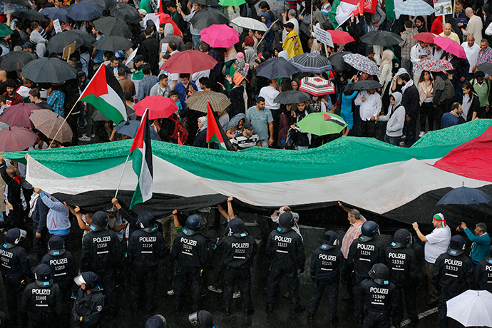 """German police watches demonstrators during a Muslim protest against the Israeli assault on the Gaza Strip in Berlin, July 25, 2014. The protest took part on the annual """"al-Quds Day"""" (Jerusalem Day) rally against the Israeli occupation of the city of Jerusalem (Reuters / Fabrizio Bensch)"""
