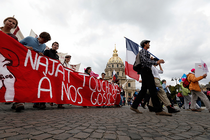 "People walk behind a banner as tens of thousands of demonstrators take part in the ""Manif Pour Tous"" (Demonstration For All) to protest against PMA (Procreation Medicalement Assistee or Medically Assisted Reproduction) and GPA (Grosesse pour Autrui or Gestation for Others) during a march in Paris October 5, 2014 (Reuters / Gonzalo Fuentes)"