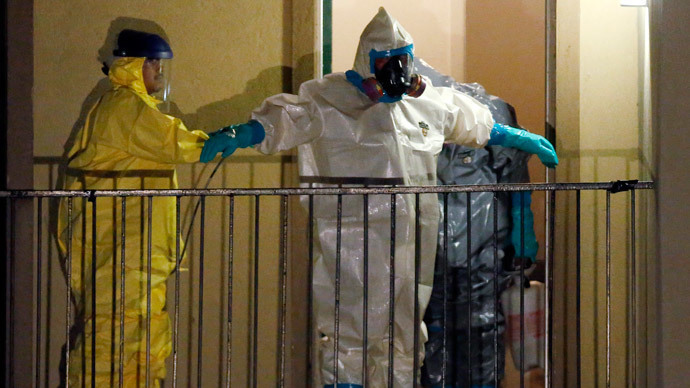 A worker in a hazardous material suit is sprayed down by a co-worker after coming out of an apartment unit where a man diagnosed with the Ebola virus was staying in Dallas, Texas, October 5, 2014.(Reuters / Jim Young)