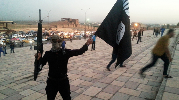 A fighter of the Islamic State of Iraq and the Levant (ISIL) holds an ISIL flag (Reuters / Stringer)