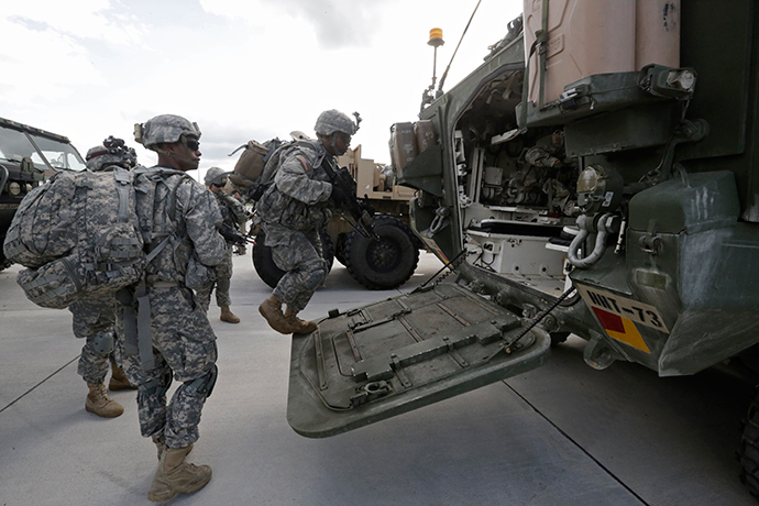 "U.S.173 airborne brigade soldiers climb onto armoured personal carrier ""Stryker"" during the ""Steadfast Javelin II"" military exercise in the Lielvarde air base, September 6, 2014 (Reuters / Ints Kalnins)"