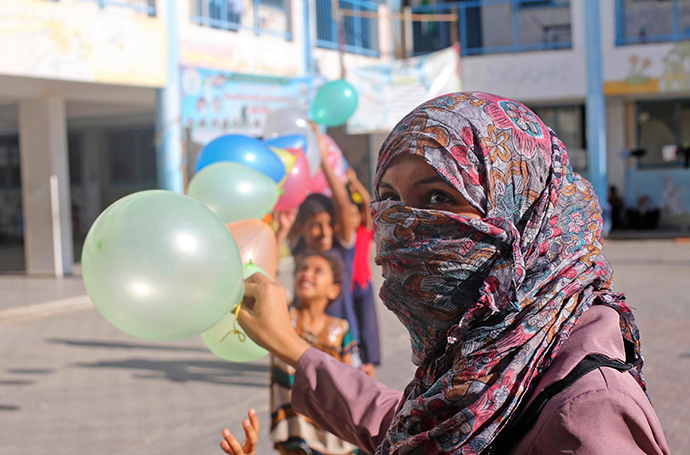Palestinians, whose houses were destroyed during a seven-week Israeli offensive, hold balloons to decorate a United Nations-run school where they take refuge ahead of Eid al-Adha in Khan Younis, in the southern Gaza Strip October 3, 2014 (Reuters / Ibraheem Abu Mustafa)