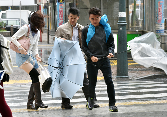 Pedestrians walk against strong wind and rain in Tokyo on October 6, 2014 (AFP Photo / Yoshikazu Tsuno)