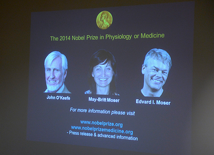 A screen presents the winners of the Nobel Prize in Medicine, U.S.-British scientist John O'Keefe and Norwegian husband and wife Edvard Moser and May-Britt Moser for their discoveries of cells that constitute a positioning system in the brain, at the Karolinska Institute in Stockholm October 6, 2014 (Reuters / Bertil Ericson)