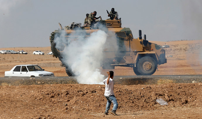 A protester throws stones at an armoured army vehicle during a pro-Kurdish demonstration in solidarity with people of Kobani, near the Mursitpinar border crossing on the Turkish-Syrian border, in the Turkish town of Suruc in southeastern Sanliurfa province October 7, 2014. (Reuters / Umit Bektas)