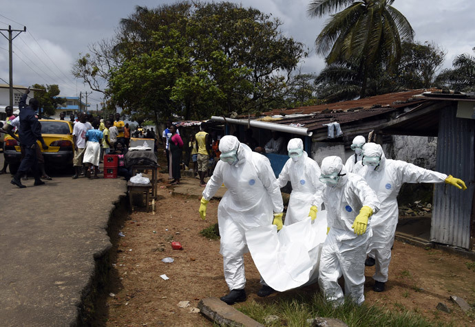 Red Cross workers carry away the body of a person suspected of dying from the Ebola virus, in the Liberian capital Monrovia, on October 4, 2014. (AFP Photo / Pascal Guyot)