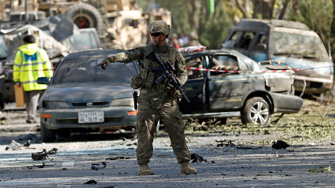 A U.S. soldier stands guard near a damaged vehicle at the site of a suicide attack in Kabul.(Reuters / Mohammad Ismail)