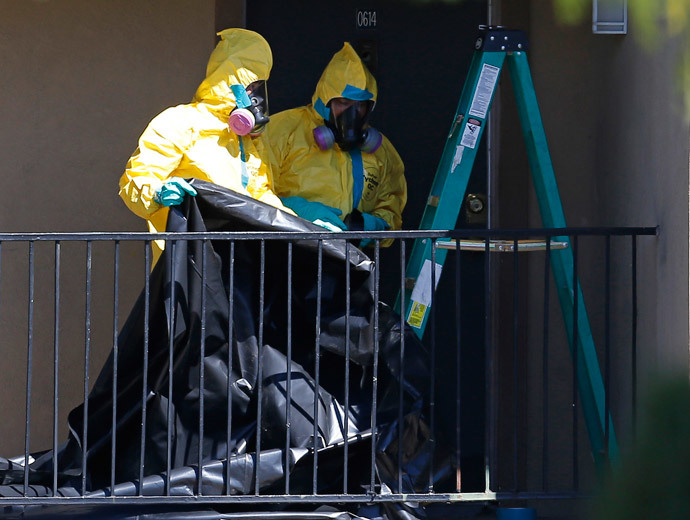 Workers wearing hazardous material suits arrive at the apartment unit where a man diagnosed with the Ebola virus was staying in Dallas, Texas, October 3, 2014. (Reuters / Jim Young)