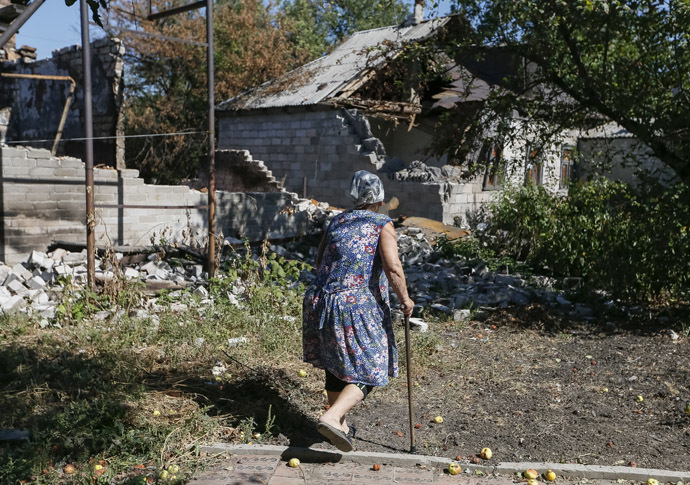 A local woman passes by near her residence which was damaged during fighting between the Ukrainian army and pro-Russian separatists, in Pervomayskoe near Donetsk September 6, 2014. (Reuters/Gleb Garanich)