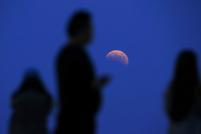 The beginning of a total lunar eclipse is seen from the Qizhong Tennis Court in Shanghai October 8, 2014. (Reuters/Aly Song)
