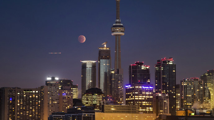 The moon turns orange during a total lunar eclipse behind the CN Tower and the skyline during moonset in Toronto October 8, 2014. (Reuters/Mark Blinch)