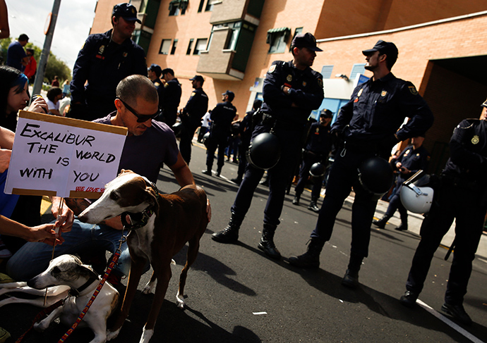 Demonstrators with pets hold signs in support of Excalibur, the dog of the Spanish nurse who contracted Ebola, outside her apartment in Alcorcon, near Madrid, October 8, 2014 (Reuters / Sergio Perez)