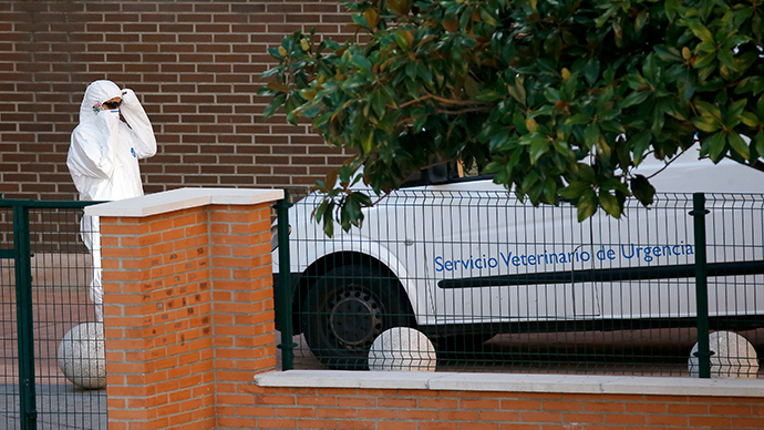 A worker adjusts protective clothing next to an emergency veterinary services vehicle parked outside the entrance of the apartment building of the nurse who contracted Ebola, in Alcorcon, outside Madrid, October 8, 2014 (Reuters / Susana Vera)