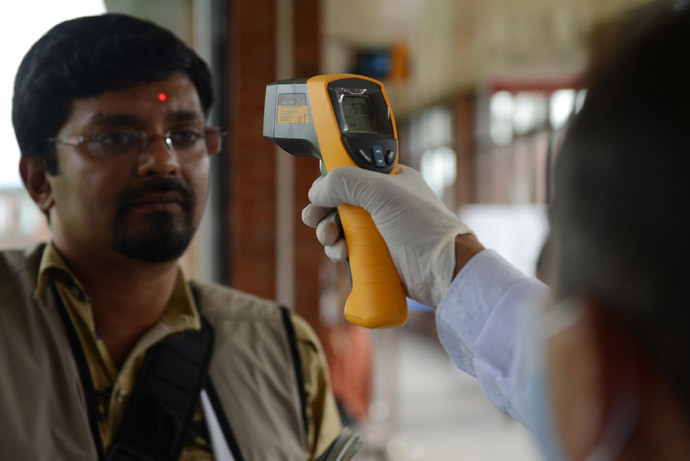A Nepalese health worker inspects an arriving passenger with an infrared thermometer for signs of fever, one of the symptoms of Ebola, at a health desk at Nepal's only international airport in Kathmandu (AFP Photo / Prakash Mathema)