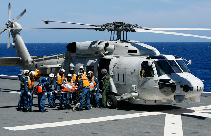 Members of the Japan Maritime Self-Defense Force (JMSDF) unload a patient from a UH 60 Seahawk in a Humanitarian Assistance and Disaster Relief drill aboard the JMSDF ship JS ISE, south of Oahu during the multi-national military exercise RIMPAC in Honolulu, Hawaii, July 12, 2014. (Reuters / Hugh Gentry)
