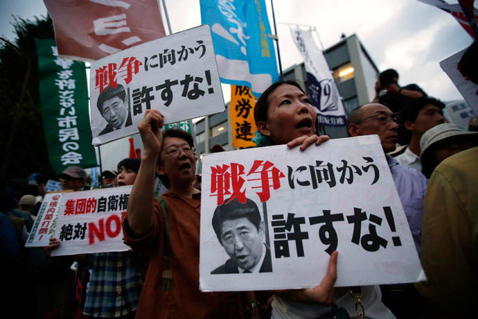 Protesters shout slogans as they hold placards during a rally against Japan's Prime Minister Shinzo Abe's push to expand Japan's military role, in front of Abe's official residence in Tokyo July 1, 2014. (Reuters / Issei Kato)